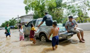 A group of people wading through a flooded street to a pick-up truck to receive containers of water.