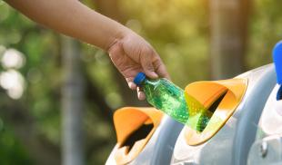 A close-up of someone throwing an empty plastic bottle into an outdoor recycling receptacle.