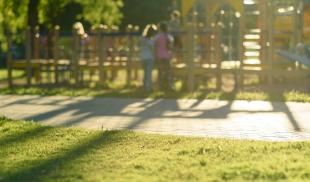 A soft focused image of children on a playground in a public park.