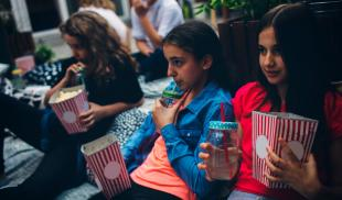 A group of children enjoy popcorn and lemonade as they watch a movie on blankets in a backyard.