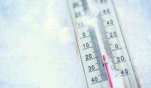 Close-up of a thermometer laying on the snow, with the temperature just below zero.