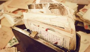 Old handwritten letters and papers are stuffed inside of a vintage handbag on a desk strewn with letters.