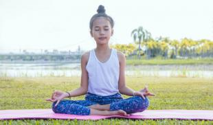 A young girl practices mediation on a pink mat outside in a nature park.