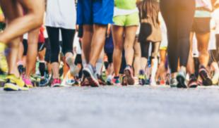The legs of a couple dozen walkers participating in a race, with pavement featured prominently in the foreground.