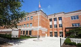 An exterior shot of a school with a flag pole in the courtyard on a sunny day.