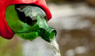 An environmental researcher wearing red rubber gloves pours water out of a green bottle.
