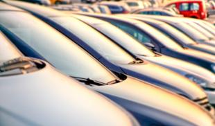 A row of parked cars on a public dealership at sunset.