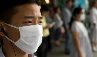 Close-Up of Asian man wearing surgical mask, with blurry people in the background standing and wearing masks as well.
