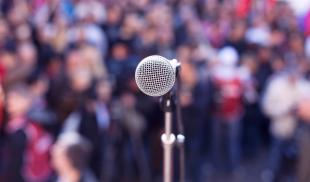 Close-up of a microphone as seen from a stage, with a blurred background of spectators at an outdoor rally.