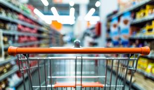 View of an empty shopping cart as seen from the perspective of the shopper, with the aisle blurred.