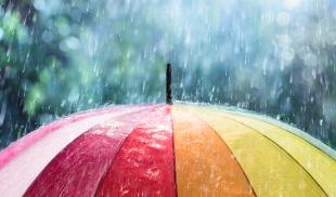 Rain falls on a rainbow-colored umbrella.