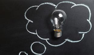 Image of a lightbulb framed by a chalkboard drawing of a thought balloon