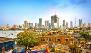 Photograph of Mumbai City, India, showing new construction of skyscrapers in the background and makeshift homes in the foreground.