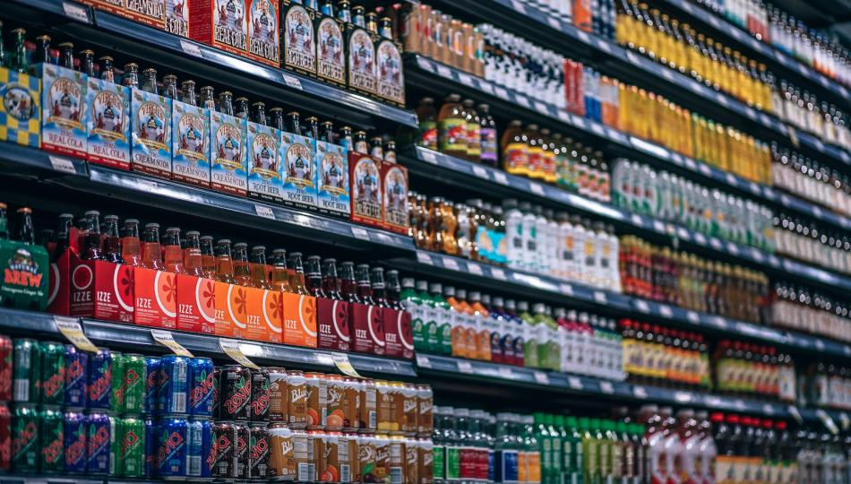 Wall of soft drinks displayed on supermarket shelves