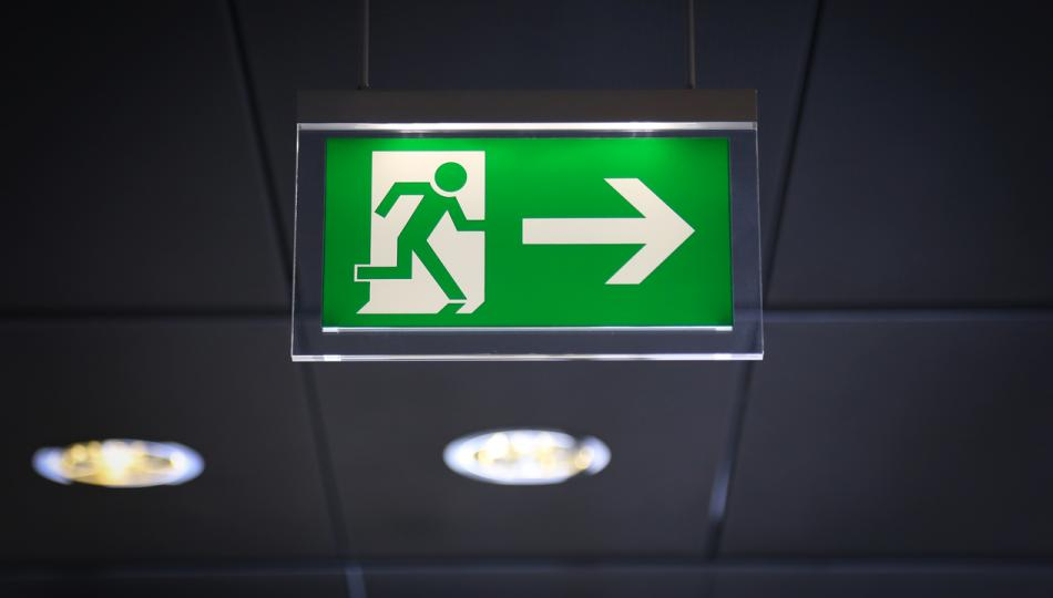 Green Emergency Exit sign with arrow and running stick figure man.