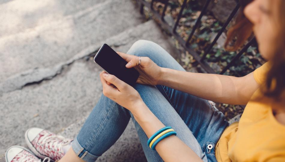 A teenage girl in jeans sits on stone steps and checks her smartphone.