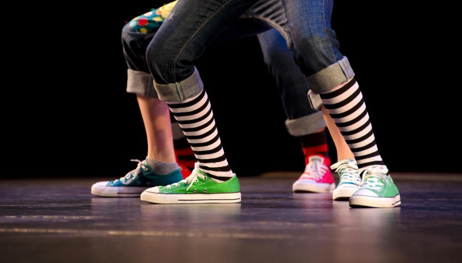 A close-up of the feet of three hip-hop dancers on stage, wearing colorful sneakers.