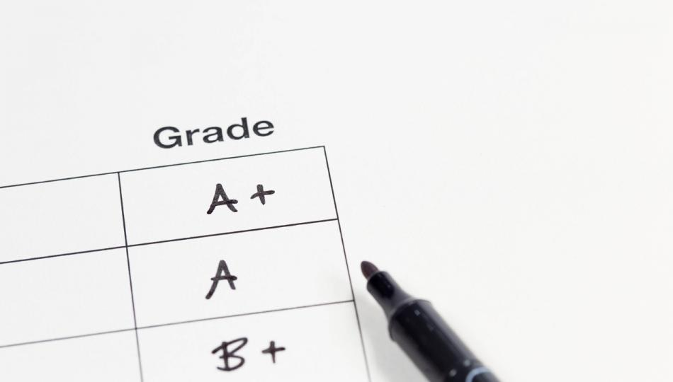 A freshly graded report card—featuring an A +, A and B + grades—with a felt-tip pen laying beside it.