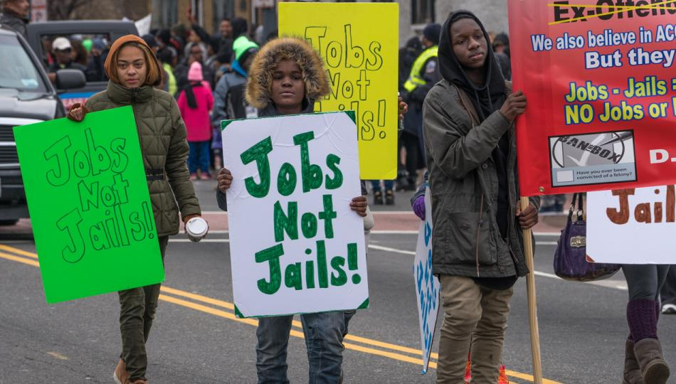 Young people waving Jobs Not Jails! signs march at a Martin Luther King, Jr. Day Peace Walk and Parade.