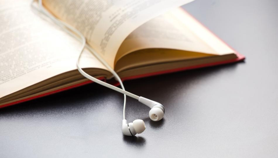A book lies open on a desk, with a pair of white ear-buds acting as a bookmark.